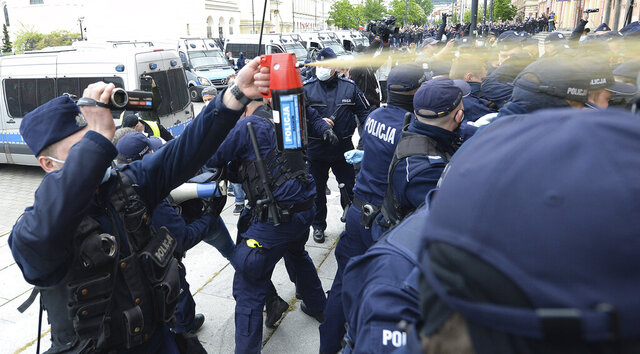 Police fire tear gas toward protesters demanding an end to economic restrictions during the coronavirus pandemic in Warsaw, Poland, Saturday, May 16, 2020. Demonstrations took part in several cities across Europe against the restrictions aimed at controlling the spread of the coronavirus, with tear gas used on protesters in Poland. (AP Photo/Czarek Sokolowski)