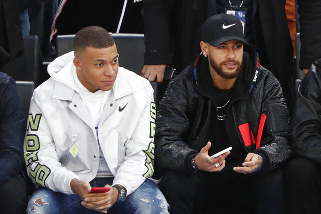 Paris St Germain's players Kylian Mbappe, left, and Neymar attend the NBA basketball match Milwaukee Bucks against Charlotte Hornets, in Paris, Friday, Jan. 24, 2020. (AP Photo/Thibault Camus)