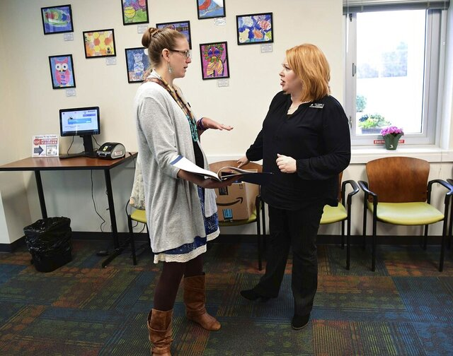 Erin Darnell, left, digital integration specialist for Anderson School District Five, talks about K3 and K4 study packets with North Pointe Elementary School Principal Jill Gilreath on Monday, March 16, 2020.(Ken Ruinard/The Independent-Mail via AP)