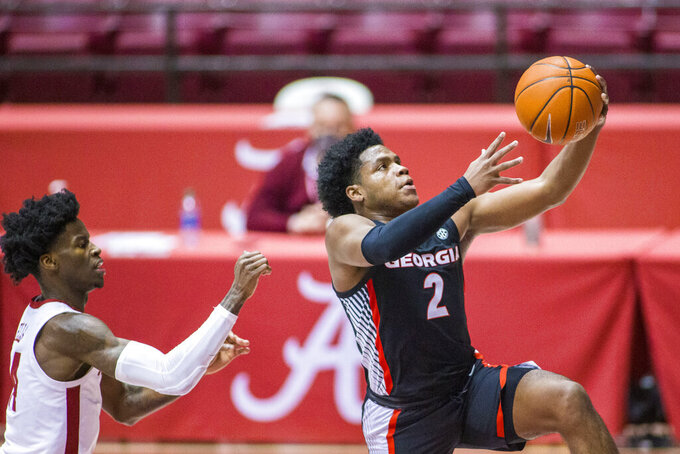 Georgia guard Sahvir Wheeler (2) gets a layup past Alabama guard Keon Ellis (14) during the first half of an NCAA basketball game on Saturday, Feb. 13, 2021, in Tuscaloosa, Ala. (AP Photo/Vasha Hunt)