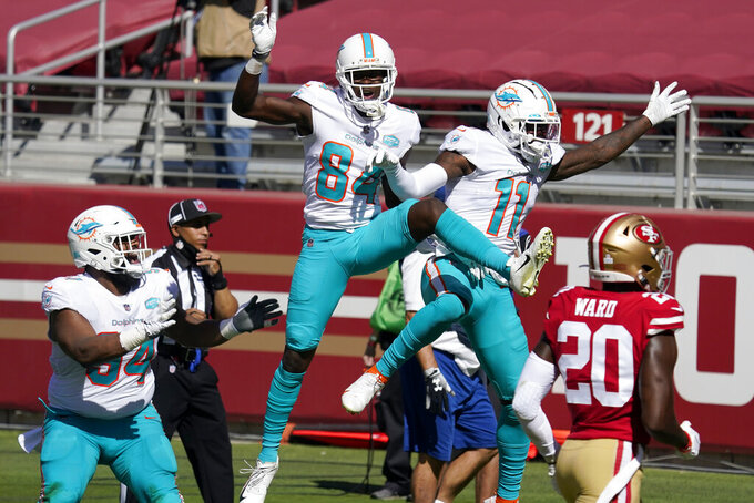 Miami Dolphins wide receiver DeVante Parker (11) celebrates after scoring against the San Francisco 49ers with wide receiver Isaiah Ford (84) and defensive tackle Christian Wilkins (94) during the first half of an NFL football game in Santa Clara, Calif., Sunday, Oct. 11, 2020. Also pictured at right is 49ers free safety Jimmie Ward (20). (AP Photo/Tony Avelar)
