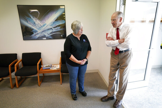 In this June 30, 2021, photo Sen. Chuck Grassley, R-Iowa, talks with General Manager Dana Ingerslev, left, before a meeting with employees at Professional Computer Solutions in Denison, Iowa. (AP Photo/Charlie Neibergall)