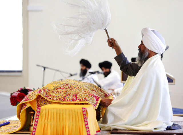 In this April 12, 2020 photo, Giani Baljinder Singh Ji leads a Sehaj Paath service for congregants watching via a livestream at Guru Nanak Mission in Oakland, N.J. Guru Nanak Mission has begun livestreaming all services due to New Jersey's order to stay at home during the coronavirus pandemic. (AP Photo/Jessie Wardarski)