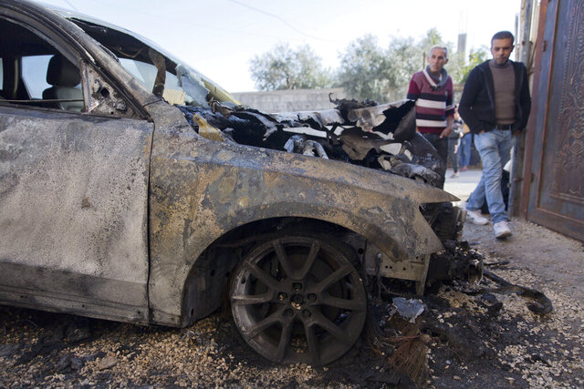 Palestinians inspect a vehicle they said was set on fire by Jewish settlers, in the village of Majdal, near the West Bank city of Nablus, Friday, Nov. 22. 2019. Israeli settlers attacked five villages in the occupied West Bank overnight, torching vehicles and olive trees, and leaving graffiti on the walls of homes, Palestinian officials said Friday. (AP Photo/Nasser Nasser)