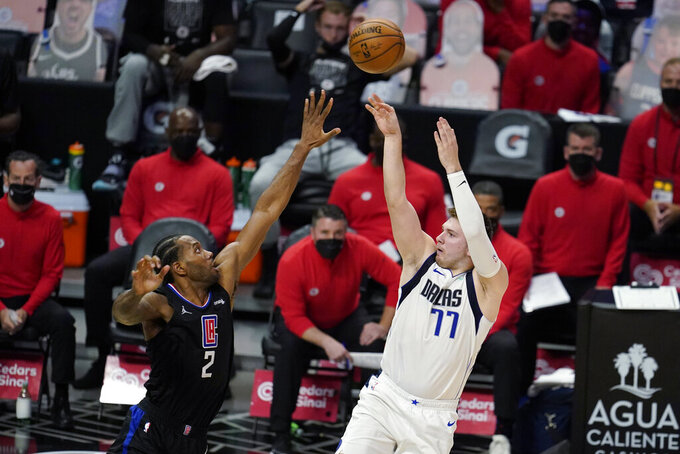 Dallas Mavericks guard Luka Doncic (77) scores over Los Angeles Clippers forward Kawhi Leonard (2) during the second half in Game 2 of an NBA basketball first-round playoff series Tuesday, May 25, 2021, in Los Angeles. (AP Photo/Marcio Jose Sanchez)