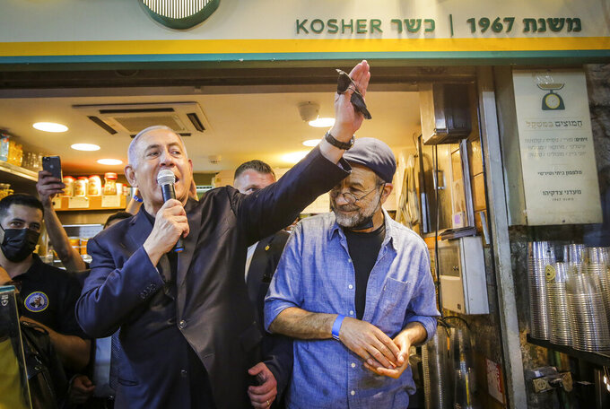 Israeli Prime Minister Benjamin Netanyahu, center, waves to supporters as he tours the Mahane Yehuda market while campaigning a day before national elections, in Jerusalem, Monday, March 22, 2021. The March 23 vote is Israel's fourth parliamentary election in two years. (AP Photo/Oren Ben Hakoon)