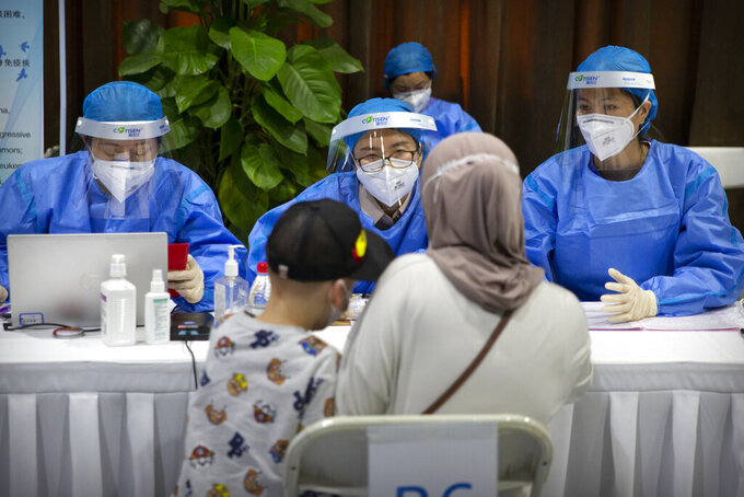 Workers wearing protective gear register a person during a COVID-19 vaccination session for resident foreign journalists at a vaccination center in Beijing, Tuesday, March 23, 2021. Chinese medical firm Sinovac said its COVID-19 vaccine is safe in children ages 3-17, based on preliminary data, and it has submitted the data to Chinese drug regulators. State-owned Sinopharm, who has two COVID-19 vaccines, is also investigating the effectiveness of its vaccines in children. (AP Photo/Mark Schiefelbein)