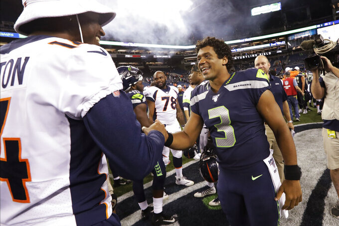 Seattle Seahawks quarterback Russell Wilson (3) greets Denver Broncos wide receiver Courtland Sutton, left, after an NFL football preseason game Thursday, Aug. 8, 2019, in Seattle. The Seahawks won 22-14. (AP Photo/Elaine Thompson)