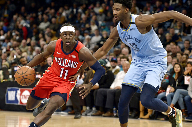 New Orleans Pelicans guard Jrue Holiday (11) drives against Memphis Grizzlies forward Jaren Jackson Jr. (13) in the first half of an NBA basketball game Monday, Jan. 20, 2020, in Memphis, Tenn. (AP Photo/Brandon Dill)