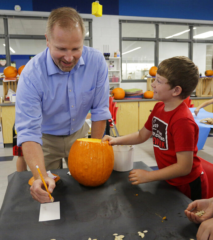 In a Wednesday, September 25, 2019 photo, Oostburg Elementary science teacher Curt Bretall, left, explains a counting procedure to be used in an experiment using pumpkins to Jonathan Walvoord, in Oostburg, Wis. (Gary C. Klein/The Sheboygan Press via AP)