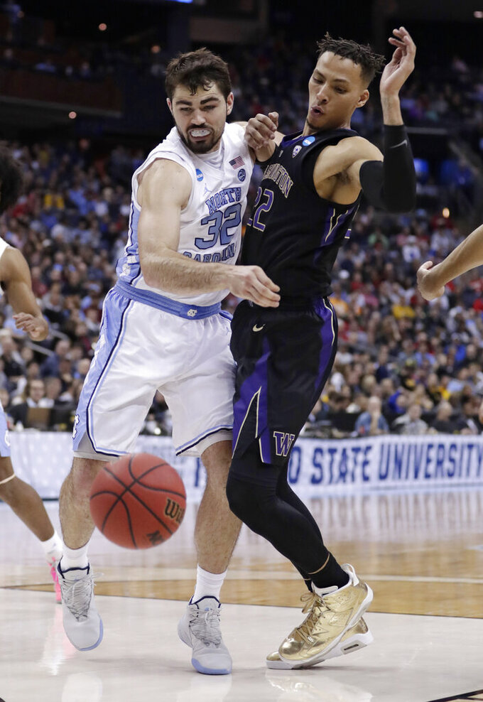 North Carolina's Luke Maye, left, and Washington's Dominic Green battle for a loose ball in the second half during a second round men's college basketball game in the NCAA Tournament in Columbus, Ohio, Sunday, March 24, 2019. North Carolina won 81-59. (AP Photo/Tony Dejak)