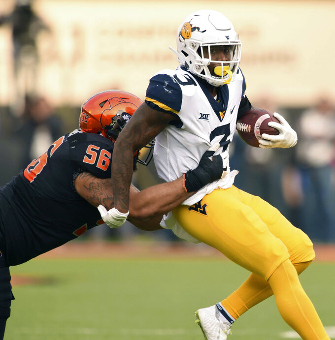 West Virginia safety Toyous Avery Jr. (3) is tackled by Oklahoma State offensive lineman Larry Williams (56) following a West Virginia interception during the first half of an NCAA college football game in Stillwater, Okla., Saturday, Nov. 17, 2018. (AP Photo/Brody Schmidt)