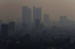 Smoke hangs over in Mexico City, Monday, May 13, 2019. Mexico City's government has warned residents to remain indoors as forest and brush fires carpeted the metropolis in a smoky haze that has alarmed even many of those accustomed to living with air pollution. (AP Photo/Marco Ugarte)