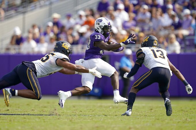 California linebacker Mo Iosefa, left, and safety Miles Williams (13) attempt to stop TCU running back Kendre Miller (33) as he carries the ball for a gain in the second half of an NCAA college football game in Fort Worth, Texas, Saturday, Sept. 11, 2021. (AP Photo/Tony Gutierrez)