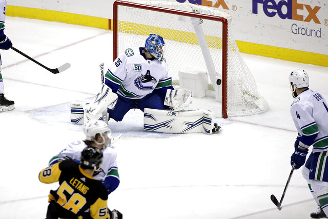 A shot by Pittsburgh Penguins' Kris Letang (58) gets past Vancouver Canucks goaltender Thatcher Demko for a goal during the third period of an NHL hockey game in Pittsburgh, Wednesday, Nov. 27, 2019. The Penguins won 8-6. (AP Photo/Gene J. Puskar)