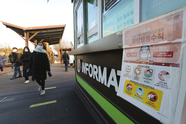 People wearing face masks pass by a poster about precautions against the coronavirus as they visit to celebrate New Year at Imjingak in Paju, near the border with North Korea, South Korea, Friday, Jan. 1, 2021. The poster reads: