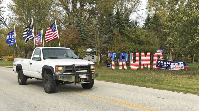 Mike Devore drives his pickup truck past a sign he made to show his support for President Donald Trump in Wayne, Ohio on Wednesday, Oct. 14, 2020. Devore lives in Wood County, an election bellwether that only once since 1964 has not picked the presidential winner. Ohio is again up for grabs in the presidential election. But only a handful of the state's counties have reliably gotten the outcome right going back over many decades.  (AP Photo/John Seewer)