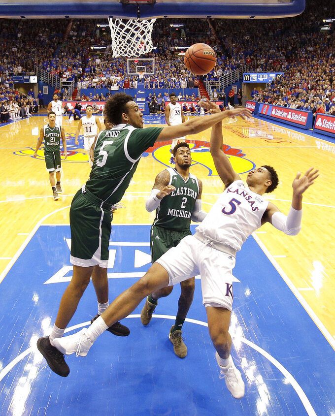 Kansas' Quentin Grimes (5) puts up a shot under pressure from Eastern Michigan's Elijah Minnie (5) during the first half of an NCAA college basketball game Saturday, Dec. 29, 2018, in Lawrence, Kan. (AP Photo/Charlie Riedel)