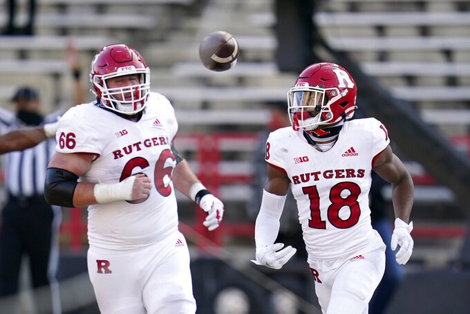 Rutgers wide receiver Bo Melton (18) and offensive lineman Nick Krimin (66) react after Melton scored a touchdown against Maryland during the second half of an NCAA college football game, Saturday, Dec. 12, 2020, in College Park, Md. Rutgers won 27-24 in overtime. (AP Photo/Julio Cortez)