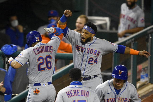 New York Mets' Robinson Chirinos (26) celebrates his two-run home run with Robinson Cano (24) during the fifth inning of the team's baseball game against the Washington Nationals, Thursday, Sept. 24, 2020, in Washington. (AP Photo/Nick Wass)