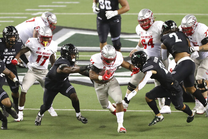 New Mexico running back Bobby Cole (34) breaks through the Hawaii defense during the first quarter of an NCAA college football game, Saturday, Nov. 7, 2020, in Honolulu. (AP Photo/Marco Garcia)