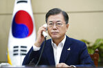 In this photo provided by South Korea Presidential Blue House, South Korean President Moon Jae-in talks on the phone with Japanese Prime Minister Yoshihide Suga at the presidential Blue House in Seoul, South Korea, Thursday, Sept. 24, 2020. Suga on Thursday held his first telephone call with his South Korean counterpart since taking office, telling Moon that the neighbors should work to resolve their strained relations.(South Korea Presidential Blue House via AP).