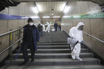 Workers wearing protective gears spray disinfectant as a precaution against the coronavirus at a subway station in Seoul, South Korea, Friday, Feb. 21, 2020. South Korea on Friday declared a