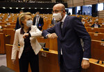 European Commission President Ursula von der Leyen, left, and European Council President Charles Michel bump elbows as they arrive at the main chamber of the European Parliament in Brussels, Thursday, July 23, 2020. European leaders took a historic step towards sharing financial burdens among the EU's 27 countries by agreeing to borrow and spend together to pull the economy out of the deep recession caused by the coronavirus outbreak (Francois Walschaerts, Pool Photo via AP)