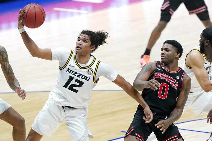 Missouri's Dru Smith (12) pulls in a rebound ahead of Georgia's K.D. Johnson (0) in the first half of an NCAA college basketball game in the Southeastern Conference Tournament Thursday, March 11, 2021, in Nashville, Tenn. (AP Photo/Mark Humphrey)