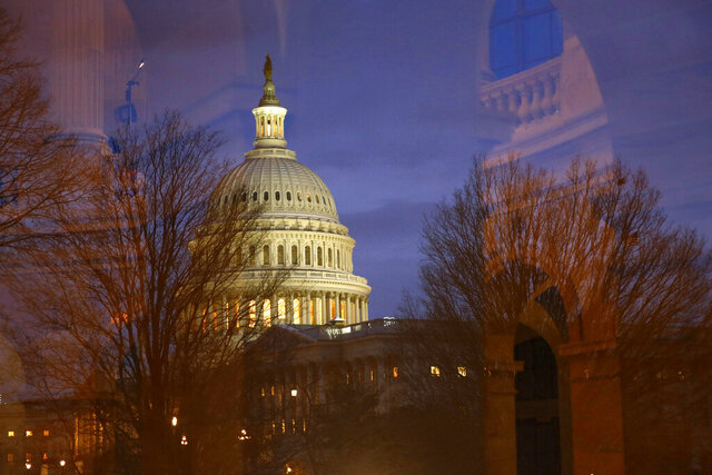 Light illuminates the U.S. Capitol dome as it is seen though window reflections in Washington, Monday, Jan. 27, 2020, during the impeachment trial of President Donald Trump on charges of abuse of power and obstruction of Congress. (AP Photo/Patrick Semansky)