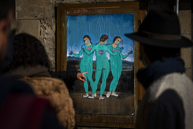 People look at a painting by Italian street artist TvBoy named