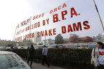 In this Oct. 17, 2018 photo, supporters of dam removals and other measures intended to help endangered orca whales stand near a large sign a outside a building in Tacoma, Wash., where the Southern Resident Killer Whale Recovery Task Force was meeting for a two-day work session. Calls to breach four hydroelectric dams in Washington state have grown louder in recent months as the plight of the critically endangered Northwest orcas has captured global attention. (AP Photo/Ted S. Warren)