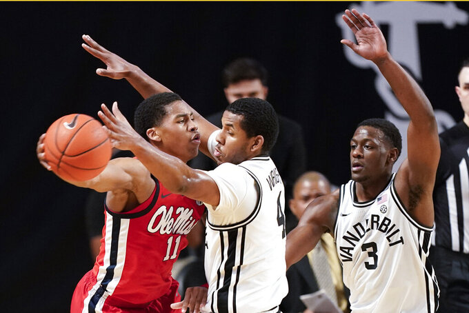 Mississippi's Matthew Murrell (11) is defended by Vanderbilt's Jordan Wright (4) and Maxwell Evans (3) in the first half of an NCAA college basketball game Saturday, Feb. 27, 2021, in Nashville, Tenn. (AP Photo/Mark Humphrey)