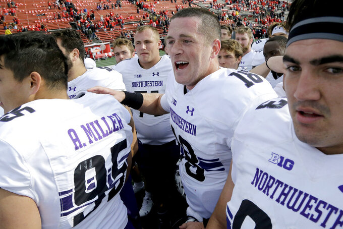 Northwestern quarterback Clayton Thorson, center right, celebrates with teammates after defeating Rutgers 18-15 during an NCAA college football game, Saturday, Oct. 20, 2018, in Piscataway, N.J. (AP Photo/Julio Cortez)