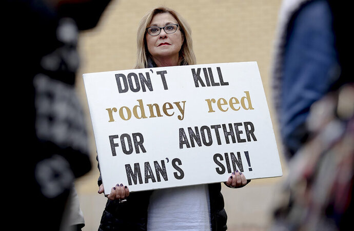 A woman holds a sign during a protest against the execution of Rodney Reed on Wednesday, Nov. 13, 2019, in Bastrop, Texas. Protesters rallied in support of Rodney Reed's campaign to stop his scheduled Nov. 20 execution for the 1996 killing of a 19-year-old Stacy Stites. New evidence in the case has led a growing number of Texas legislators, religious leaders and celebrities to press Gov. Greg Abbott to intervene. (Nick Wagner/Austin American-Statesman via AP)