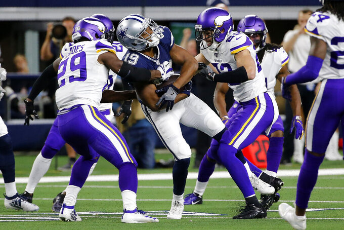 Dallas Cowboys wide receiver Amari Cooper (19) catches a pass and is stopped by Minnesota Vikings' Xavier Rhodes (29) and Harrison Smith, right, during the second half of an NFL football game in Arlington, Texas, Sunday, Nov. 10, 2019. (AP Photo/Michael Ainsworth)