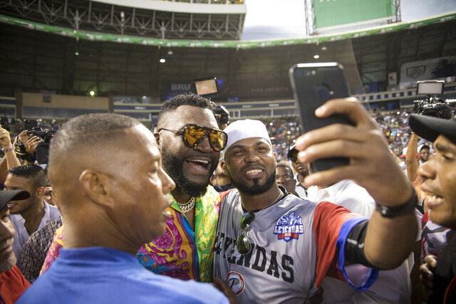 Legendary Boston Red Sox slugger David Ortiz poses for a photo with a fan after making a surprise appearance at the Day of Legends baseball event at the Quisqueya Stadium, in Santo Domingo, Dominican Republic, Sunday, Dec. 8, 2019. The Dominican-American retired professional baseball player was shot in the back in his native country six months ago by a hired gunman who drove up on a motorcycle and fired at close range, hitting him in the torso. They said the intended target was another man. (AP Photo/Tatiana Fernandez)