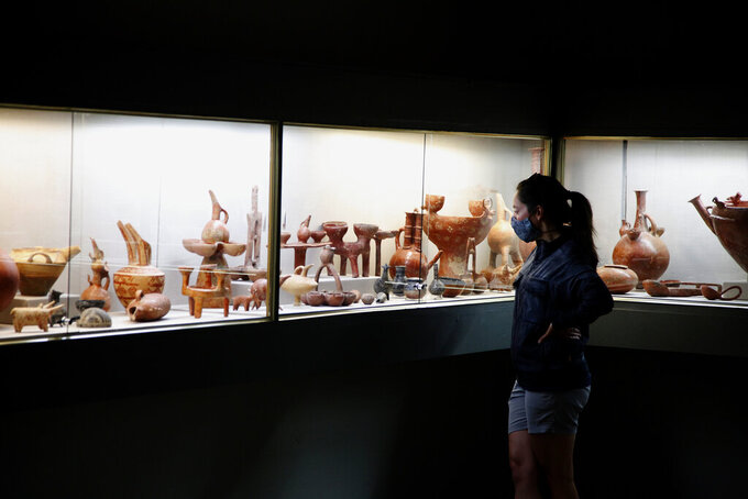 A visitor wearing a mask to protect against the coronavirus looks at ancient artifacts placed inside a glass-protected display area at Cyprus Archaeological Museum in the capital Nicosia, on Thursday, June 18, 2020. Cyprus' museums opened to the public earlier this month as the government gradually lifted most of a string of tough restrictions imposed in March to check the spread of the coronavirus. (AP Photo/Petros Karadjias)