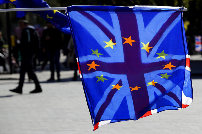 A British Union flag is flown behind a European Union flag during demonstrations near Parliament in London, Wednesday, April 10, 2019.   Just days away from a no-deal Brexit, European Union leaders meet Wednesday to discuss granting the United Kingdom a new delay to its departure from the bloc. (AP Photo/Kirsty Wigglesworth)