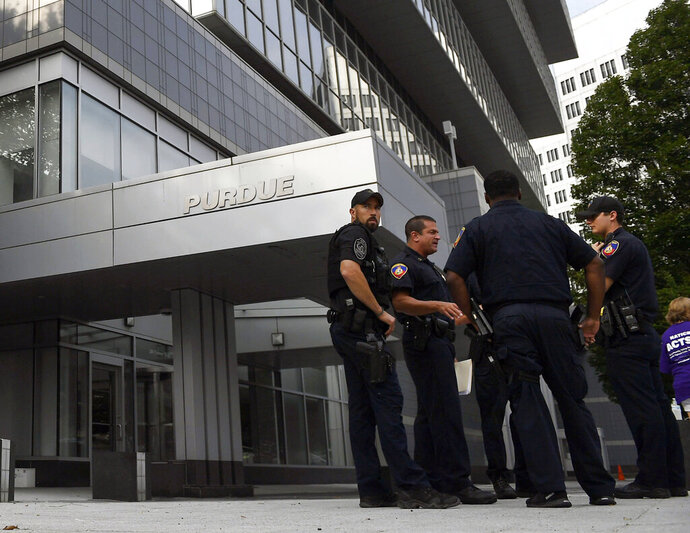 In this Aug. 17, 2018 photo, Stamford Police stand outside the headquarters of Purdue Pharma, which is owned by the Sackler family, in Stamford, Conn. The Sackler family came under scrutiny when a legal filing in Massachusetts gave detailed allegations of how family members and other Purdue Pharma executives sought to push prescriptions for the drug OxyContin and downplay its addiction risks. (AP Photo/Jessica Hill)