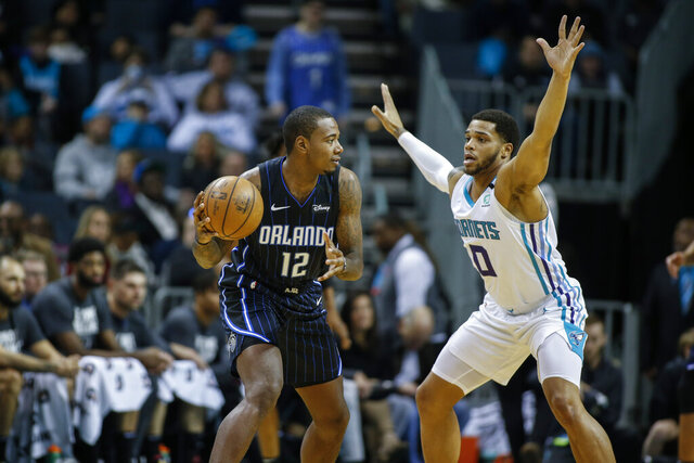 Orlando Magic forward Gary Clark, left, looks to pass around Charlotte Hornets forward Miles Bridges in the first half of an NBA basketball game in Charlotte, N.C., Monday, Jan. 20, 2020. (AP Photo/Nell Redmond)