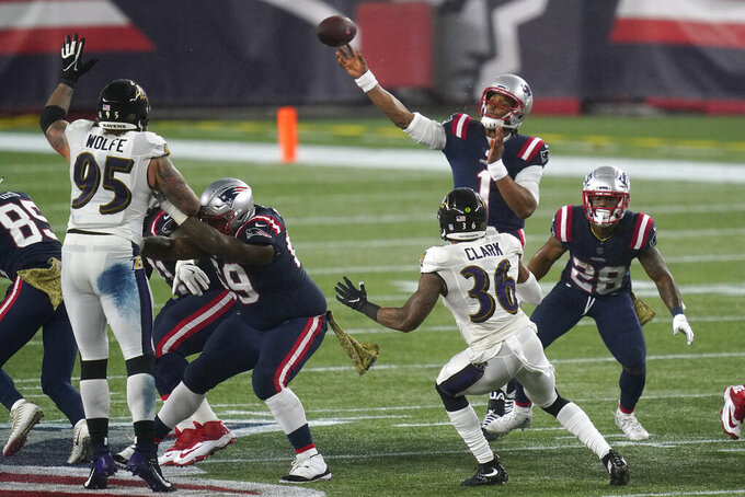 New England Patriots quarterback Cam Newton passes under pressure from Baltimore Ravens defensive end Derek Wolfe (95) and safety Chuck Clark (36) in the first half of an NFL football game, Sunday, Nov. 15, 2020, in Foxborough, Mass. (AP Photo/Elise Amendola)