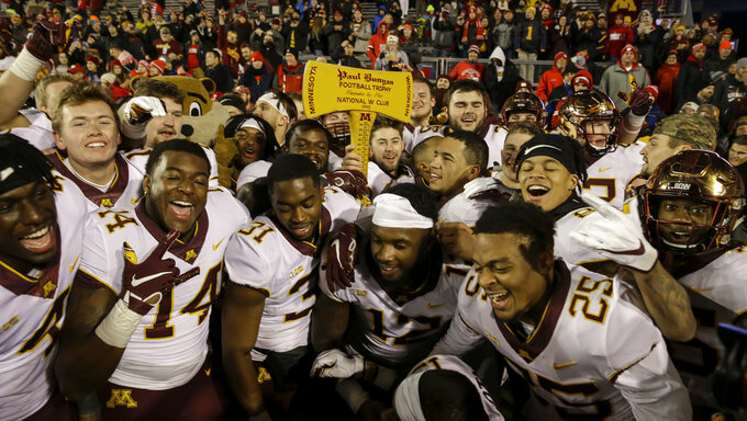 Minnesota players celebrate with the Paul Bunyan Axe trophy after beating Wisconsin 37-15 in an NCAA college football game Saturday, Nov. 24, 2018, in Madison, Wis. (AP Photo/Andy Manis)