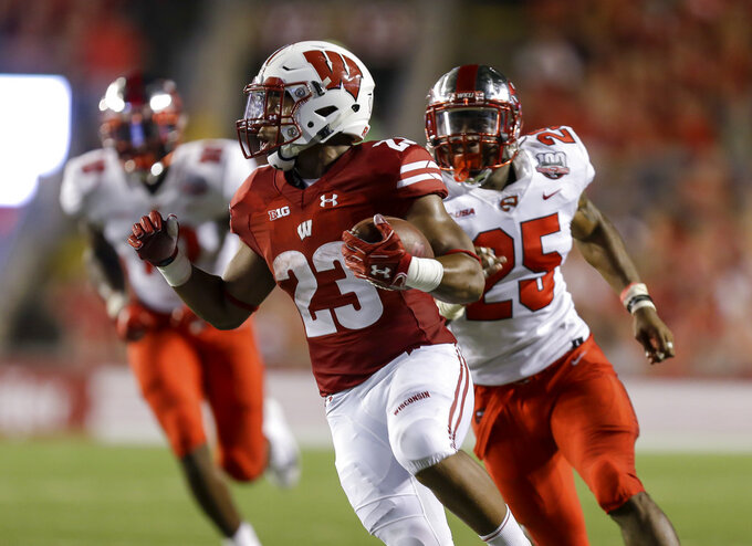 Wisconsin running back Jonathan Taylor runs for a touchdown as Western Kentucky linebacker Masai Whyte (25) give chase during the first half of an NCAA college football game Friday, Aug. 31, 2018, in Madison, Wis. (AP Photo/Andy Manis)