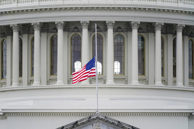 An American flag flies at half-staff in remembrance of U.S. Capitol Police Officer Brian Sicknick above the Capitol Building in Washington, Friday, Jan. 8, 2021. Sicknick died from injuries sustained as President Donald Trump's supporters stormed the Capitol. (AP Photo/Patrick Semansky)