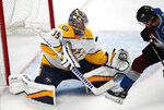 Nashville Predators goaltender Pekka Rinne, left, deflects a shot off the stick of Colorado Avalanche left wing Gabriel Bourque in the first period of Game 3 of an NHL hockey first-round playoff series Monday, April 16, 2018, in Denver. (AP Photo/David Zalubowski)
