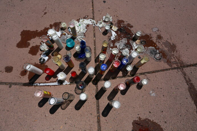 Candles melt in the sun at an impromptu memorial for Fedonta