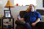 Ed Bisch, who lost his 18-year-old son Eddie to an overdose nearly 20 years ago, listens on speaker phone from his home in Westampton, N.J., to a bankruptcy judge Wednesday, Sept. 1, 2021, on a plan for OxyContin maker Purdue Pharma to settle thousands of lawsuits brought by state and local governments and others over opioids. Bisch, who has spent more than a decade pushing for the Sacklers to be criminally prosecuted, is leading a group of families that are asking the U.S. Justice Department to appeal the settlement. (AP Photo/Matt Rourke)