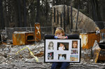 FILE - In this Feb. 7, 2019, file photo, Christina Taft, the daughter of Camp Fire victim Victoria Taft, displays a collage of photos of her mother, at the burned out ruins of the Paradise, Calif., home where she died in 2018. Pacific Gas & Electric officials are to be expected to appear in court Tuesday, June 16, 2020, to plead guilty for the deadly wildfire that nearly wiped out the Northern California town of Paradise in 2018. (AP Photo/Rich Pedroncelli, File)