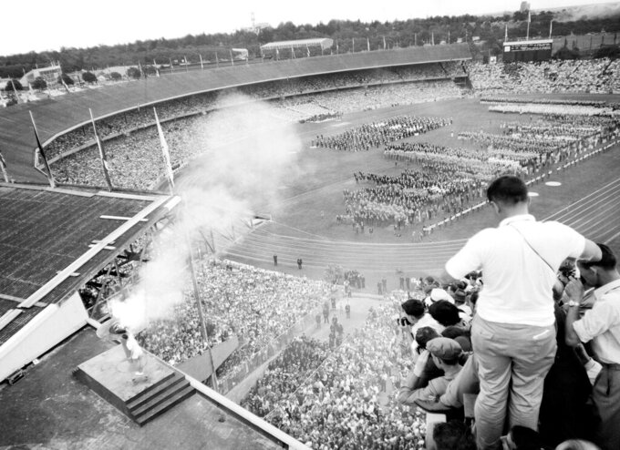 Australian athlete Ron Clark, bottom left, plunges the Olympic torch into the bronze bowl, to light the Olympic flame, which will burn throughout the XVI Olympic Games, in Melbourne, Australia, Nov. 22, 1956. (AP Photo)